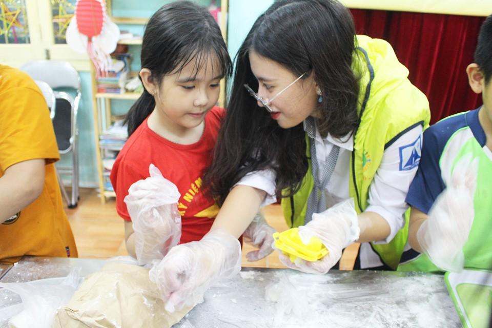 Vân Anh hướng dẫn các bạn nhỏ tại Nhà nuôi dưỡng trẻ em hữu nghị Đống Đa nặn bánh trung thu.